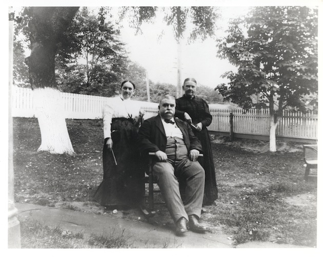 The photograph, taken circa 1900, shows John Schneider's wife, Mary Gallagher Schneider; her brother, Francis X. Gallagher; and Ozella Ellis Schneider, wife of Louis Schneider. Beyond the whitewashed trees and fences of the Schneider family's front yard lies the intersection of 32nd Street (Wisconsin Avenue) and Schneider's Lane, which ran a little south of what is now Calvert Street.