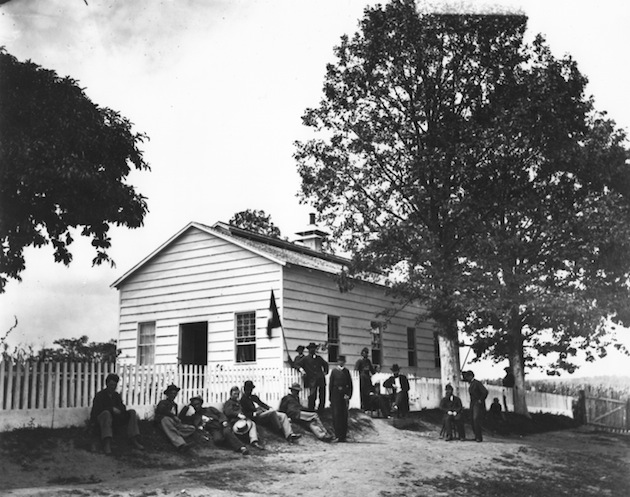 The Signal Camp hospital, on the occasion of the closing of the Signal Camp, August, 1865. Col. Benjamin F. Fisher, Chief Signal Officer of the Army, is seated in front of the whitewashed tree. The seated man to his left, wearing a white vest and a civilian coat, is his predecessor, Albert Myer, who had been relieved of his command. (Myer has occasionally been misidentified as Charles Sabin Taft. The confusion may have arisen because of Myer's civilian clothes, and because Taft––a military surgeon who was at Ford's Theater when Lincoln was shot––is known to have spent the day of the assassination at the Signal Camp hospital.)