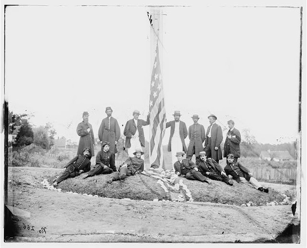 Flag Lowering at the Signal Camp, August 1865. Albert Myer (seen grasping the lowered flag) is not in uniform because competion with the Secretary of War for control of military telegraphy had cost him his command. At far left, hand tucked in coat, is Benjamin F. Fisher, who escaped from a Confederate prison in 1864.